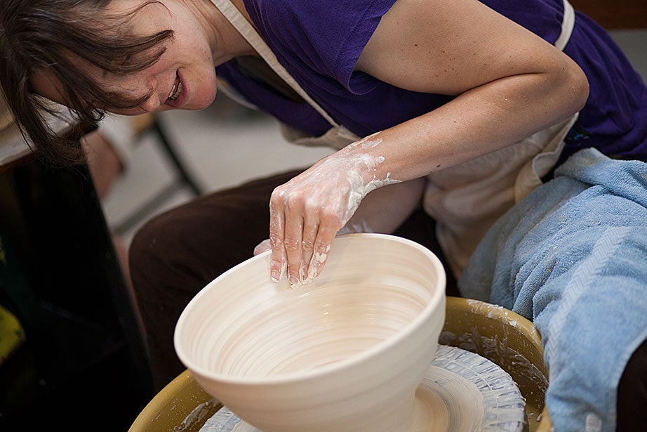 Instructor Monica Ripley tapers and shapes the sides of her porcelain bowl.