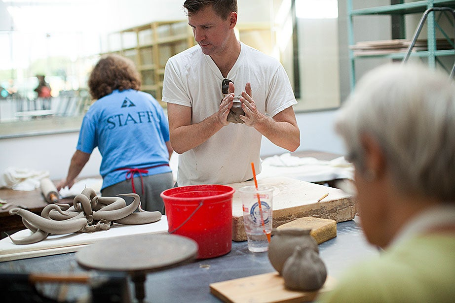 Christopher Adam '94 works diligently among the other ceramics students.