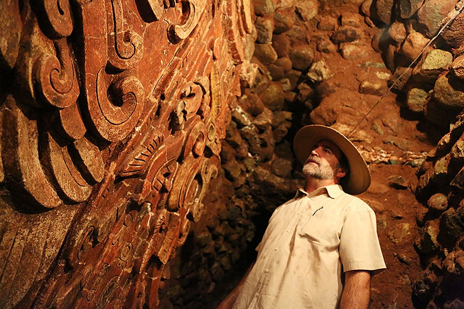 "William Fash, Harvard's Bowditch Professor of Central American and Mexican Archaeology and Ethnology, examines a polychrome plaster relief of the name of the founding king of the Copán dynasty, K'inich Yax K'uk' Mo,' on a temple (nicknamed ""Margarita"" by the archaeologists) that is located deep inside a series of tunnels burrowing through the main ruins' acropolis."