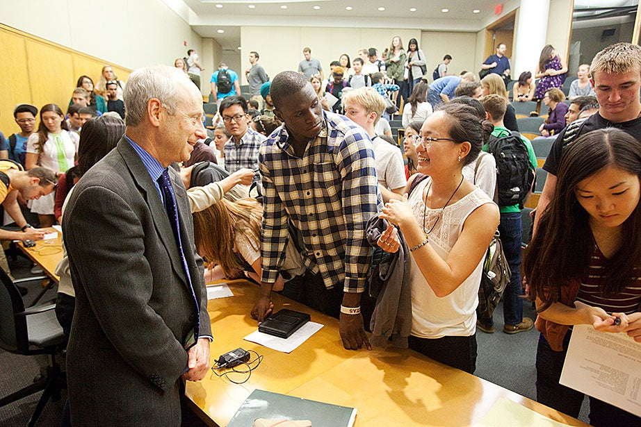 Anne T. and Robert M. Bass Professor of Government Michael Sandel talks with students following class. Jon Chase/Harvard Staff Photographer