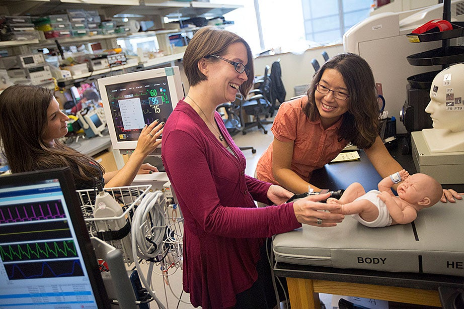 Staff engineer-mechanical Stacey Fitzgibbons (from left), and electrical staff engineers Amanda Wozniak and Crystal Knodel test a medical device developed at the Wyss Institute for treating infant apnea. On the table is a plastic infant used for calibrating the equipment.