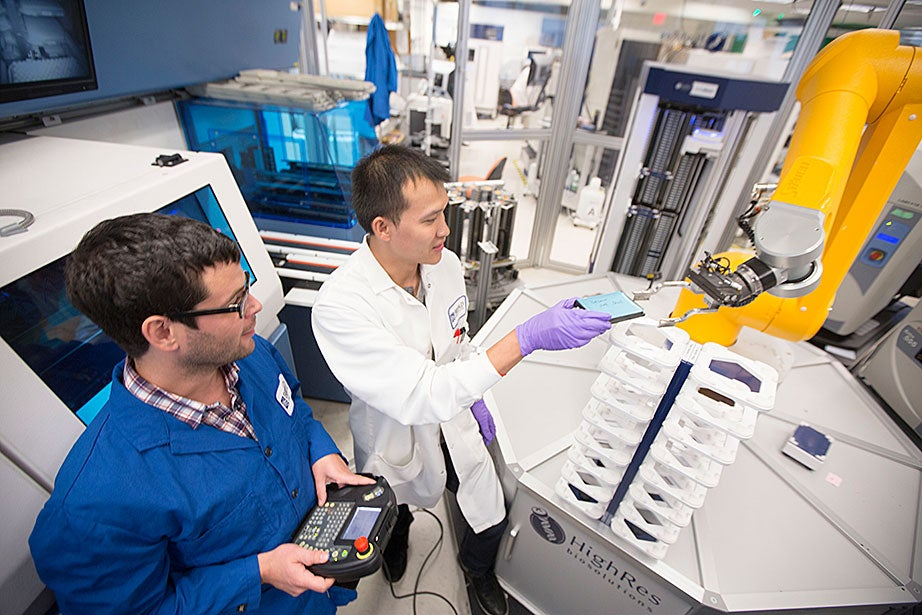 Broad Institute automation engineer Christian Soule (left) and research associate Hoang Danh perform high-throughput screening and compound management investigating cancer, infectious diseases, pesticide, and bacteria.