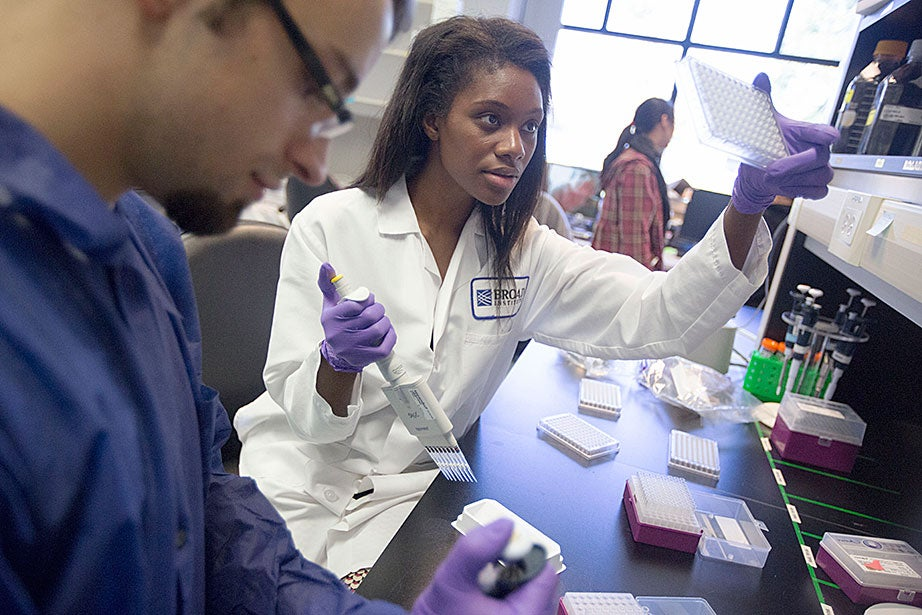 Cassandra Elie and Kevin Joseph, both process development associates, perform whole genome sample sequencing inside the Broad Institute.