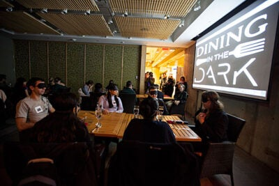 Dining in the Dark gathered around 30 participants from the Harvard Graduate School of Education. Students Cass Walker (left) and Nina Boonyaleepun fumbled to greet each other (photo 2) — because all students were required to wear blindfolds upon entry (photo 3).