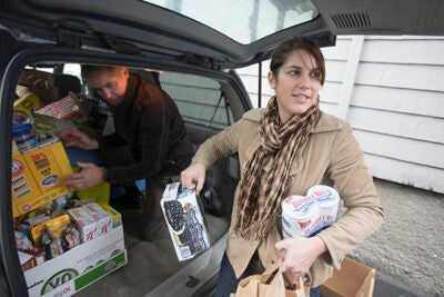 Graduate students helped bring more than 2,000 cans of food to the Greater Boston Food Bank, including Harvard Kennedy School (HKS) student Christina L. Marin and her father, Bruce Long, HBS '82 (photo 1), Phillip Harding (photo 2), also of HKS, and Leon Liu from the Graduate School of Arts and Sciences (photo 3).