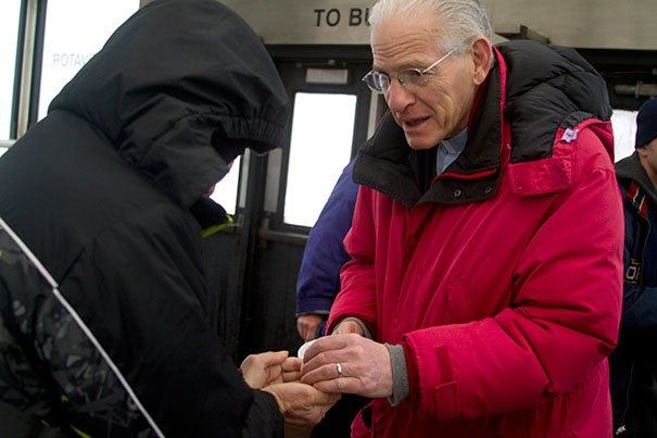 The Rev. Jedediah Mannis gives communion to an attendee at a Sunday morning service of the Outdoor Church of Cambridge at the Porter Square MBTA stop.