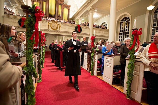 """""""They are great tunes,"""" said Harvard choirmaster Edward E. Jones of """"Jingle Bells"""" and """"Sleigh Ride"""" — traditional holiday songs with a Harvard connection. Jones is seen here leading the 104th Annual Christmas Carols Service in Memorial Church."""