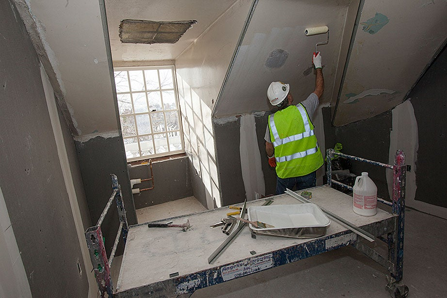 Worker Carlo Bonito applies plaster to the walls of a suite in McKinlock.