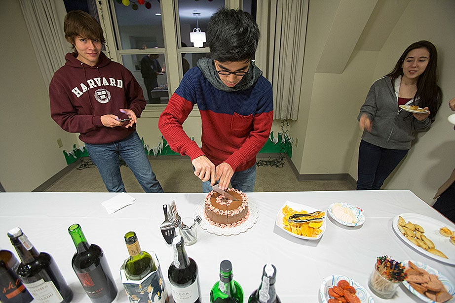 """Leverett House """"Not Just Sherry Hour"""": Kelly Maeshiro '14 (left) watches as Benjamin Antillon '14 cuts a cake at swing housing at 20-62 DeWolfe."""