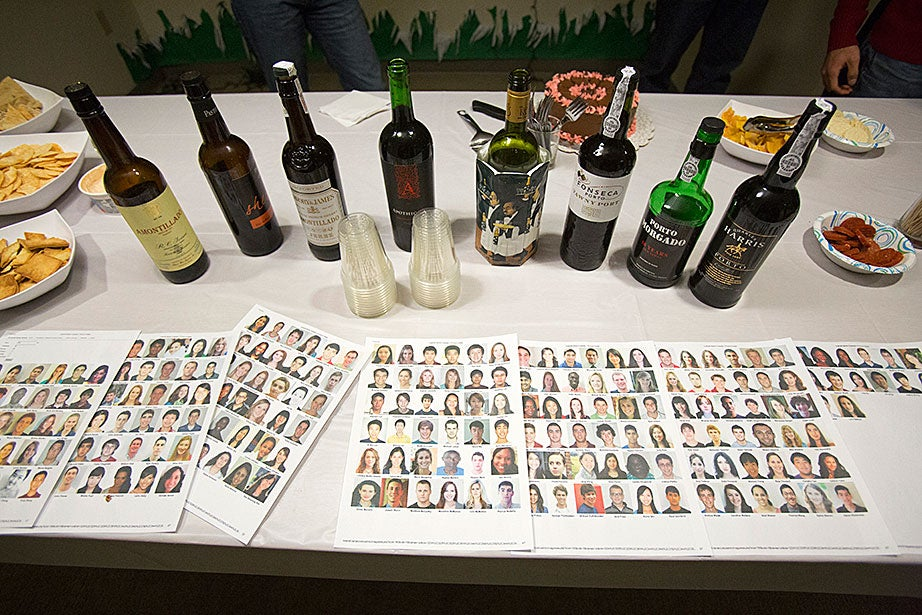 """Not Just Sherry Hour"" at swing housing at 20-60 DeWolfe: Sherry bottles frame headshot photos of Leverett residents, placed so guests can connect a face with a name."