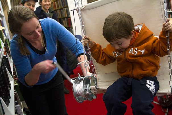 "Alexandra ""Lexi"" Bond, a GSD student studying the design future of concert halls, hoisted Ethan Robinson, 3, using ""Extra Leverage"" — a contraption of metal, chain link, and canvas that allows a library-goer to hoist herself or himself to a high shelf. ""I'm interested in dynamic models,"" said Bond."