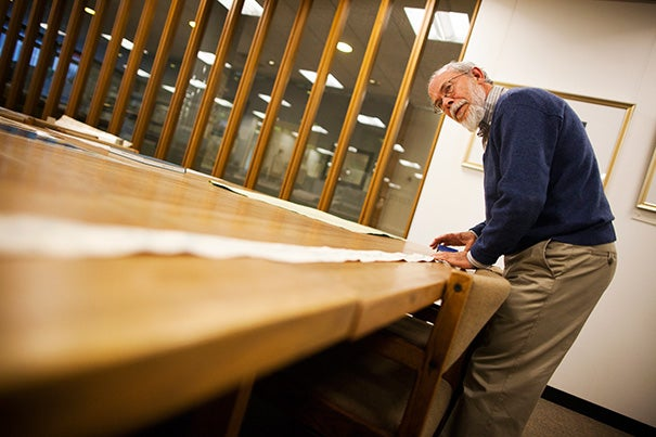 Research librarian Joseph Garver unrolls a Chinese scroll map from 1865, the longest in the collection. It was purchased by John King Fairbank, Harvard's first full-time professor of Chinese history.
