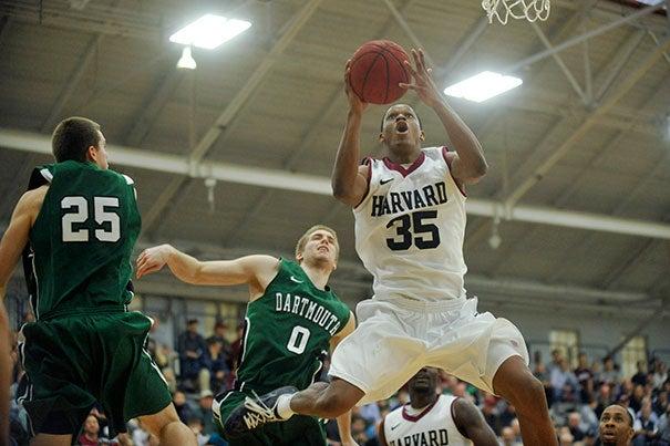 Harvard men's basketball v. Dartmouth. Crimson forward Agunwa Okolie '16 goes up for a dunk past a pair of Dartmouth defenders.