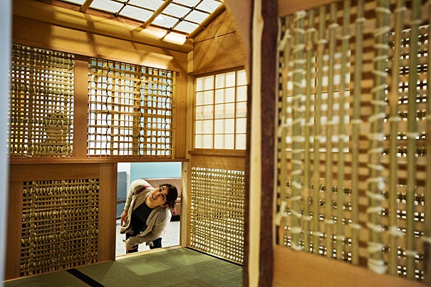 "GSD student Joanna Rodriguez-Noyola examines a Japanese tea house (photo 1) set up at Harvard's CGIS for ""The Thinking Hand"" exhibit. Akinori Abo, a master carpenter from Japan, demonstrates the tools, techniques, and woods of traditional Japanese carpentry (photos 2 and 3)."