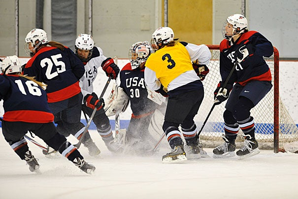 The U.S. Olympic women's hockey squad practices at Belmont Hill School under Harvard coach Katey Stone (photo 1). Of the 20 players, three are Harvard students and one is a Harvard alum. All four are pictured in keepsake cards (photos 2 and 3).