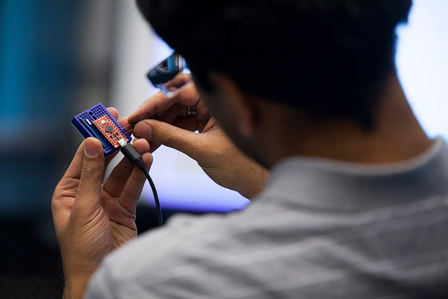 Avinash Uttamchandani, a preceptor in electrical engineering at the School of Engineering and Applied Sciences, holds the inner workings of a computer mouse. Stephanie Mitchell/Harvard Staff Photographer