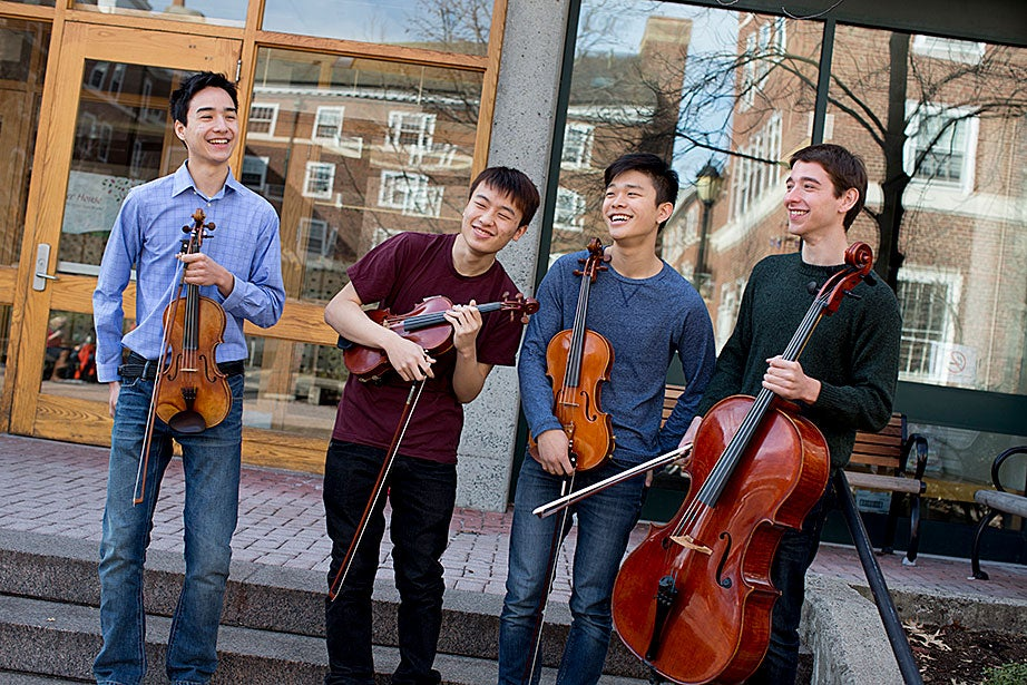 With the quad reflected in Currier's front entryway, the four musicians posed for a group photo: David Roberts '16, violin (from left); Albert Li '16, violin; Jiho Kang '16, viola; and Sascha Bercovitch '14, cello.