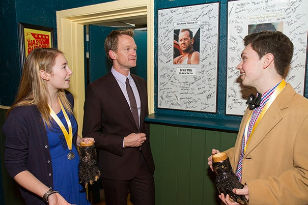 Hasty's Man of the Year Neil Patrick Harris (center) toured the Hasty Pudding Institute on Winthrop Street. The tour offered photos of past recipients of the Pudding Pot, including Bruce Willis. Leading the tour were Chaffee Duckers '16 (left) and Robert Fitzpatrick '16. Harris with his own Pudding Pot (photo 2).