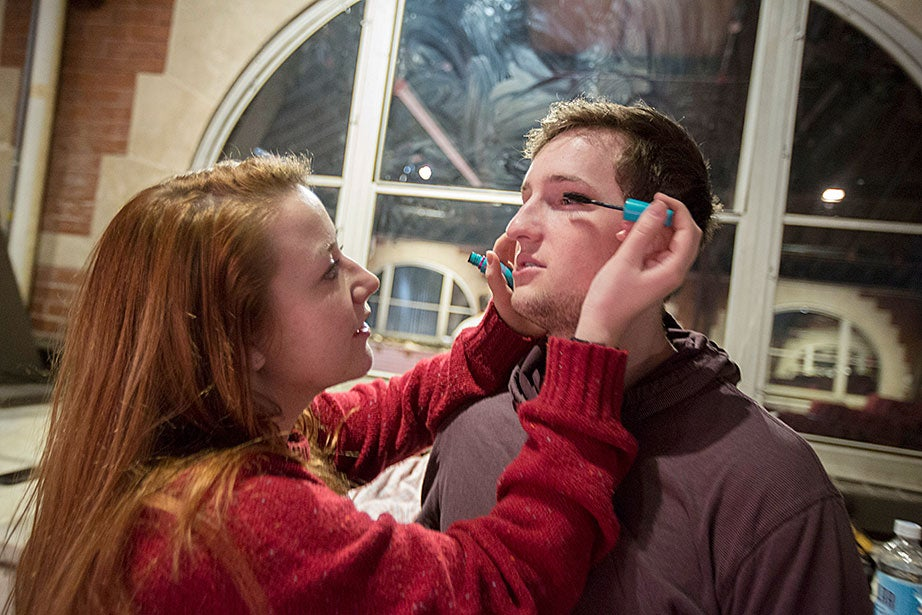 Taylor Phillips '13 (left) applies mascara to Matt Bialo '15 during rehearsal.