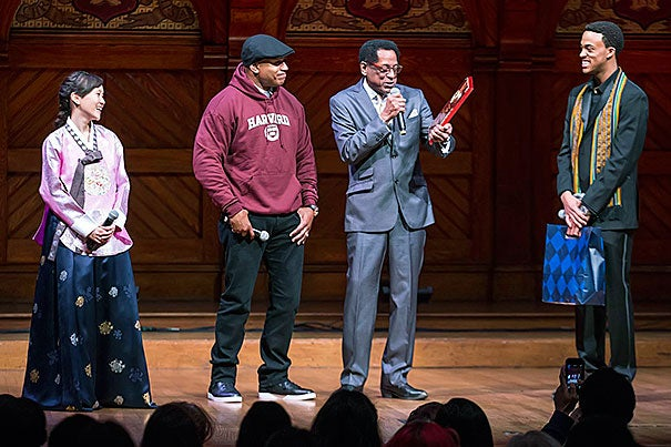"LL Cool J (second from left) was presented  the Harvard Foundation's Artist of the Year award by S. Allen Counter. ""There's been no one more committed to young people's education than LL Cool J,"" Counter said. Aubrey Walker '15 and Soyoung Kim '14,  co-directors of Cultural Rhythms, shared the Sanders Theatre stage during Saturday's award presentation."