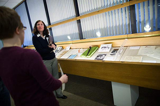 """Sharyn Nolan (right) and Juliana Kuipers lead visitors through """"Code Books to 'Love Story': Staff Selections from the Harvard University Archives' Collections."""" This inaugural staff exhibit, eccentric and surprising, is up through May 15."""