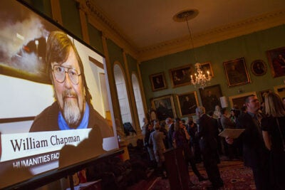 The contributions of 52 Faculty of Arts and Sciences employees were recognized at the Dean's Distinction Awards ceremony on Thursday. William Chapman of Humanities Faculty Services had his image projected onto a large screen (photo 1) at the University Hall reception. FAS Dean Michael D. Smith (from left, photo 2) applauded Lauren Szufat, Aatiyah Paulding, Gretchen Gingo, and Bob Daley, all from the Form I-9 Process Team. Linda Wang (center, photo 3) from the Economics Department posed with family members Anna and Sean Li.