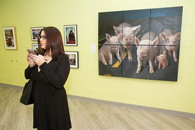 """""""Beasts of Burden"""" features the work of 13 artists. The Ed Portal exhibit examines our complicated connections to animals. Mary Davos stands by a painting of pigs titled """"Nothing Here for You."""""""