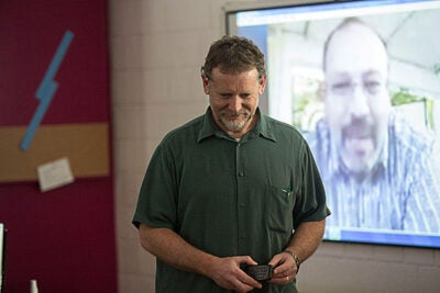 "Cambridge Rindge and Latin teacher Paul McGuinness (from left, photo 1) arranged to have his students Skype with Harvard Professor Peter Girguis, who was in the Alvin submarine. ""The opportunity for all kinds of students to talk face-to-face to the people on a vessel like that, answering questions in the moment, is really valuable,"" said CRLS senior Caspian Harding  (from left, photo 2), who sat next to fellow student Clio Macrakis during the presentation."