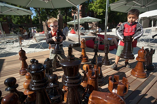 Daniel Reyes, 3 years old and Karl Ikerman, 2 (glasses) years old play a game of giant chess while harvard students use social media on their smart phones in the background at the Science Center plaza at Harvard University. Kris Snibbe/Harvard Staff Photographer