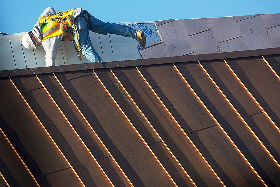 A construction worker completes a copper roof during the renovation of the Tozzer Library.