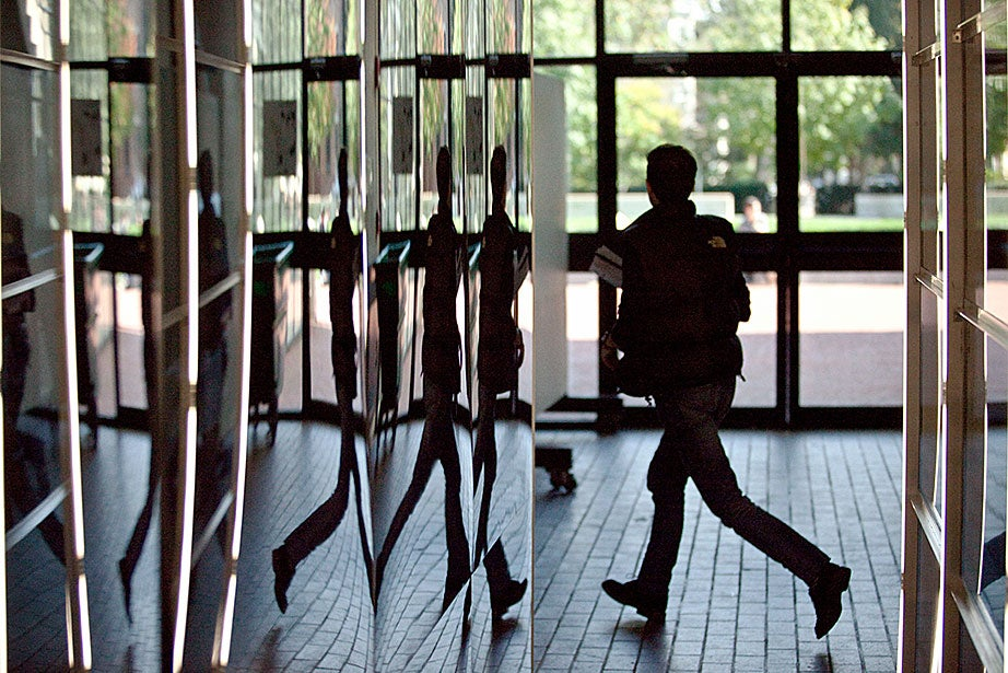 A student rushes past exhibition mirrors inside Gund Hall at the Harvard Graduate School of Design.