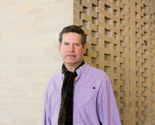 Christopher E.G. Benfey stands before the Harkness Commons wall designed by his great-uncle, Josef Albers.