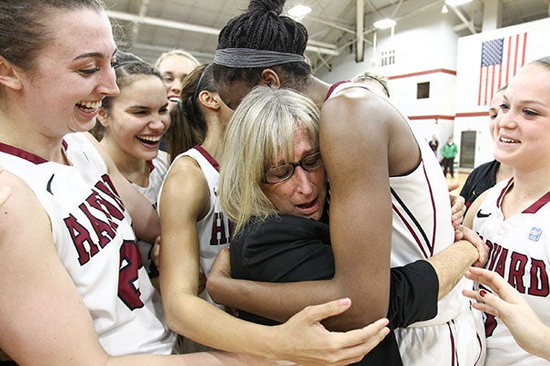 Harvard women's basketball head coach Kathy Delaney-Smith got a team hug after earning her 515th career win, breaking the record held by a former Princeton coach. Harvard beat Yale, 69-65.