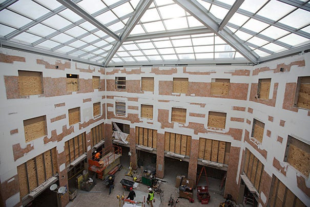 Workers renovate the Inn at Harvard as part of the House renewal and swing space projects (photos 1, 2). An artist's rendering shows what the atrium will look like upon completion (image 3).