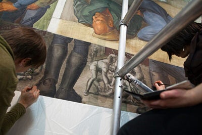 The fresco was created in 1933 by Harvard graduate and realist painter Lewis Rubenstein and his collaborator, Italian-born artist Rico Lebrun, as a teaching tool for students eager to observe firsthand the art of fresco painting. Here, conservators restore some of the fresco's details inside the museum.