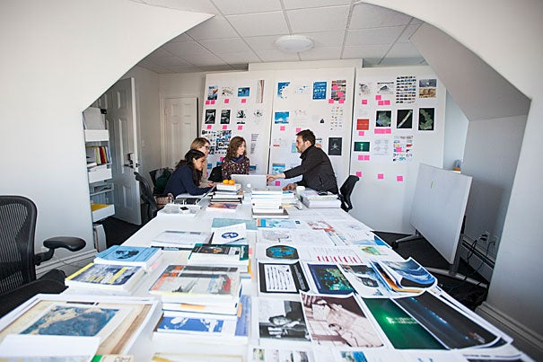"In a Graduate School of Design office, students Phoebe White (from left), Erin Wythoff, and Adriana Chávez have a deep conversation on urbanized oceans with Associate Professor of Landscape Architecture Pierre Bélanger. ""They're mapping the industrialization of the ocean,"" said Bélanger. ""We're looking at the future."""