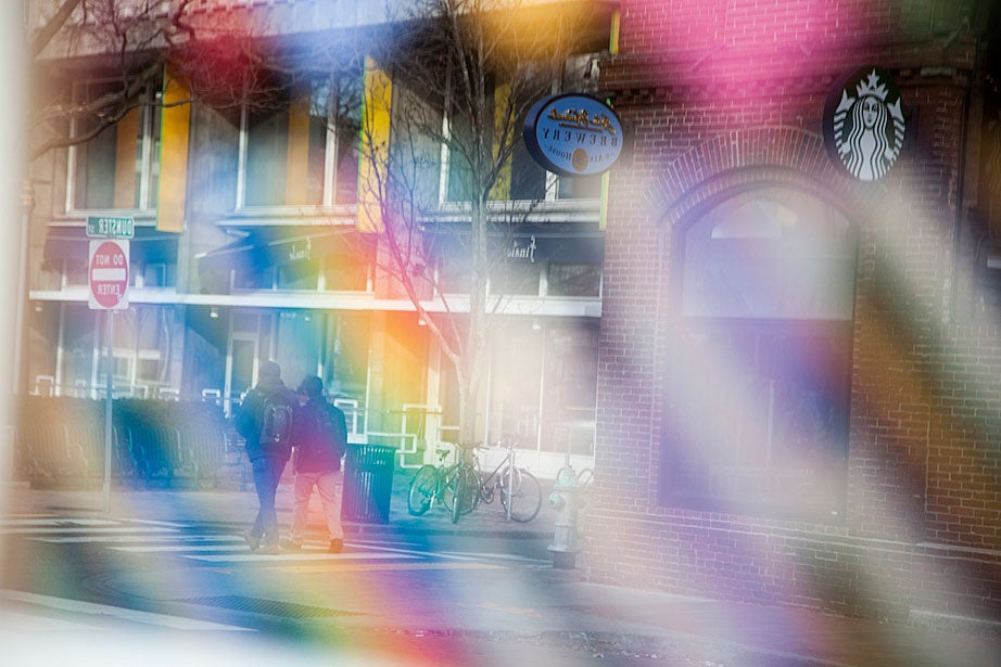 Two students are reflected off the vibrant window display of neckties at a men's clothier on the corners of Mt. Auburn and Dunster streets.