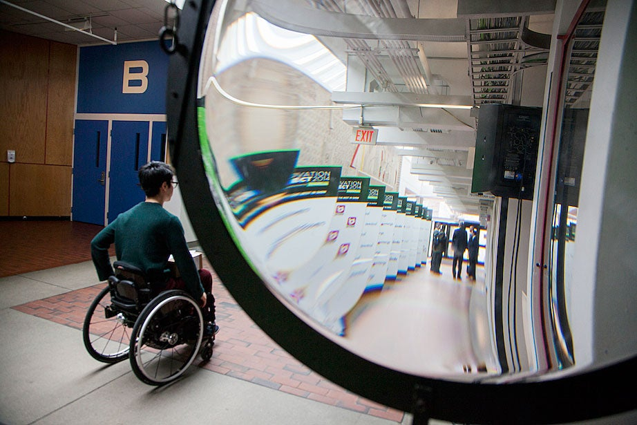 A convex glass structure distorts the view of men chatting in the basement of the Science Center as a man in a wheelchair enters the frame.