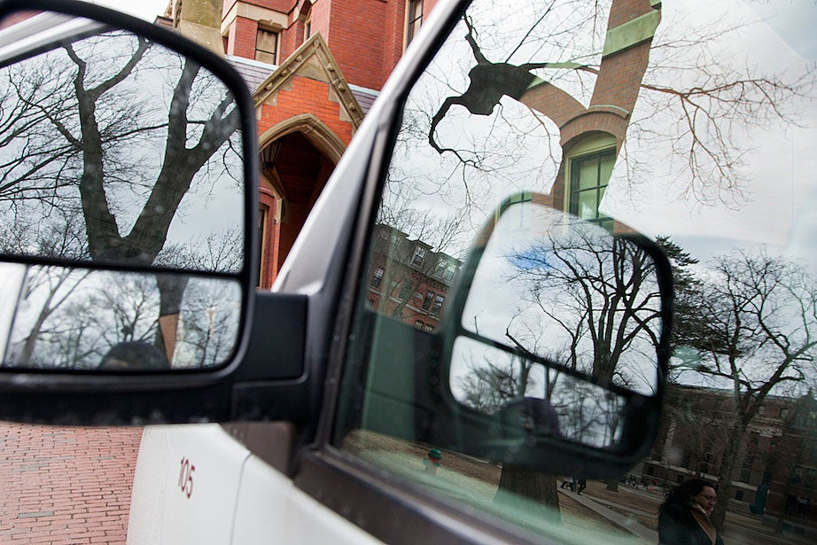 A University van reflects pedestrians and views of Harvard Yard on its window.