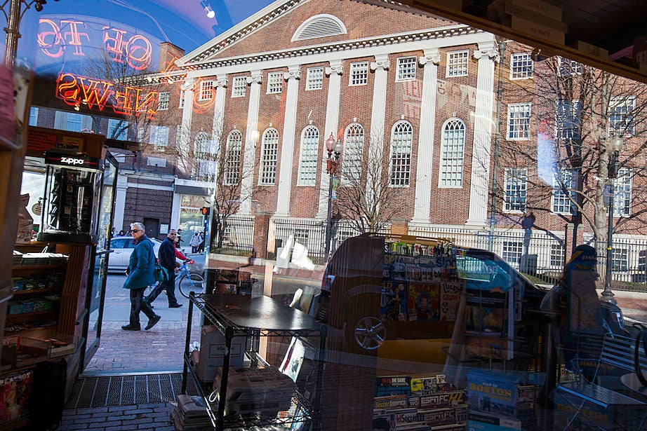Pedestrians, bicyclists, and cars pass through a Harvard Square shop's windows, with views of Lehman Hall.