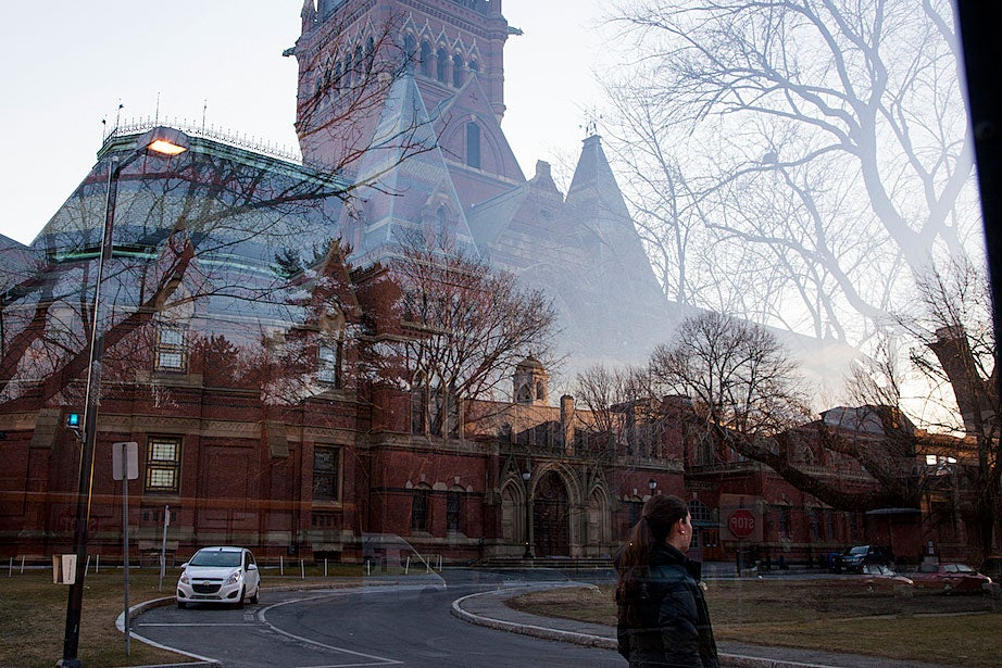 A student waits for the shuttle at Memorial Hall as Adolphus Busch Hall is seen in its reflection.