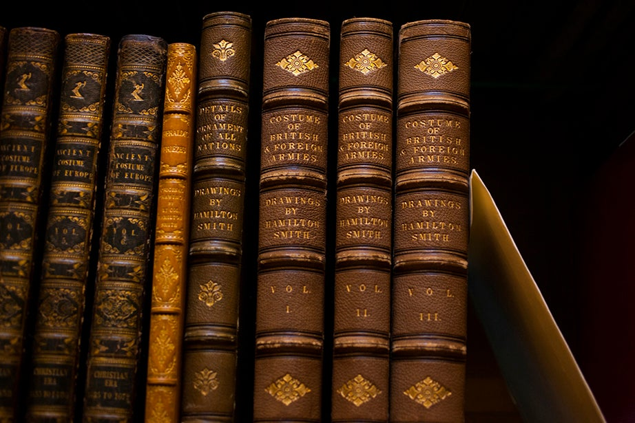 "Volumes of ""Costume of British & Foreign Armies"" are part of the collection. The slip of white paper next to the books holds the place of a borrowed item."
