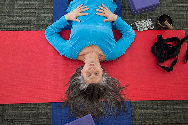 "Marianne Bergonzi leads a yoga practice for Harvard employees at Monks Library. Bergonzi experienced her first yoga practice when she was 50 years old.  ""It was life changing. I had to pass the yogic philosophy onto people who might never get a chance to learn [the] body, mind and breath connection.""  Photo by: Melanie Rieders"