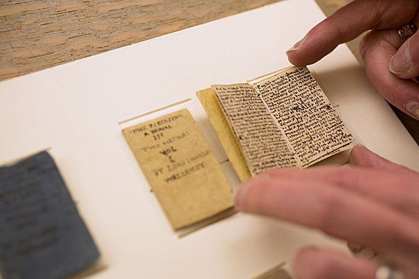 """Nine miniature manuscript books (photos 1, 3), six by Charlotte Brontë and three by Patrick Branwell Brontë, are part of the collections at Houghton Library. The library repaired, rehoused, and digitized the books, which are nearly 200 years old. """"These tiny books help to evoke the whole experience of the Brontë children,"""" says Houghton curator Leslie Morris (photo 2)."""