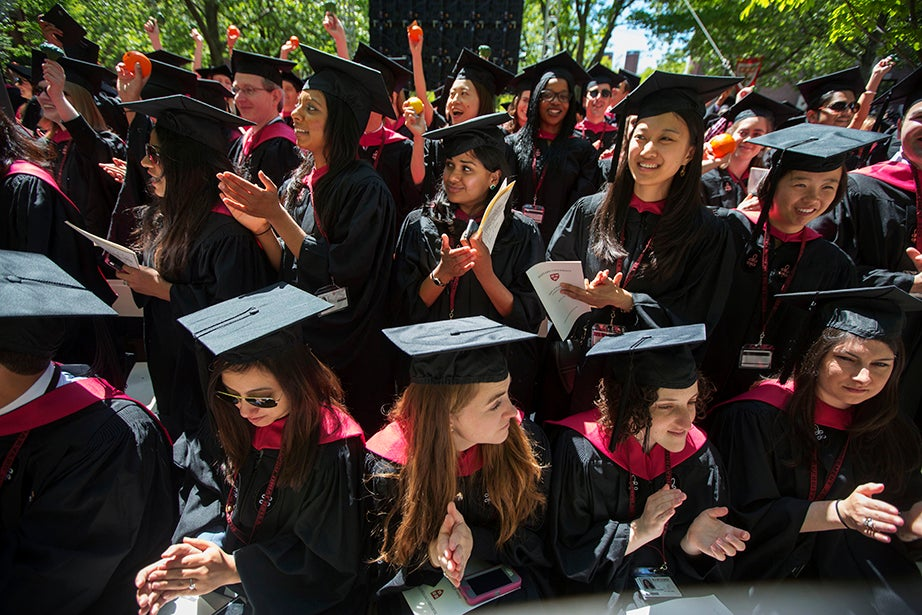 Shilpa Murthy (top row, from left), Kanchana Amaratunga, and Jennifer Cai cheer on fellow graduates. Kris Snibbe/Harvard Staff Photographer