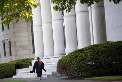 Harvard University celebrates Commencement 2014. A graduate passes Littauer Building. Stephanie Mitchell/Harvard Staff Photographer