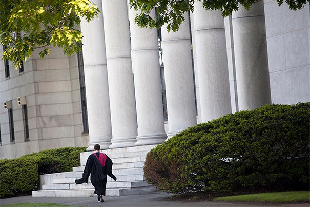 Harvard University celebrates Commencement 2014. A graduate passes Littauer Building. Stephanie Mitchell/Harvard Staff Photographer