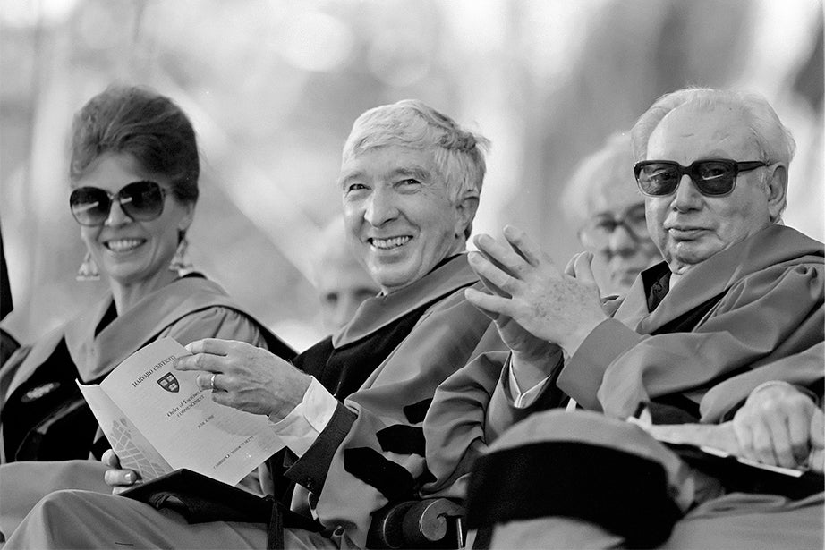 Author John Updike (center) acknowledges applause after receiving his honorary degree at Harvard Commencement in 1992. Updike is flanked by molecular biologist Joan Argetsinger Steitz and violin virtuoso Isaac Stern. Jon Chase/Harvard Staff Photographer