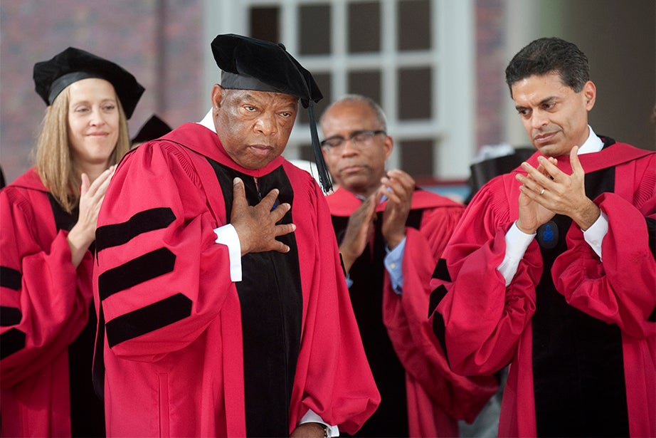 John Lewis (center), U.S. representative from Georgia since 1987, is touched by the audience's ovation at the 2012 Commencement. A leader of the Civil Rights Movement, Lewis became nationally known during his prominent role in the Selma-to-Montgomery marches in 1965. Despite numerous beatings, Lewis emerged as a leader for his courage and commitment to nonviolence. Jon Chase/Harvard Staff Photographer