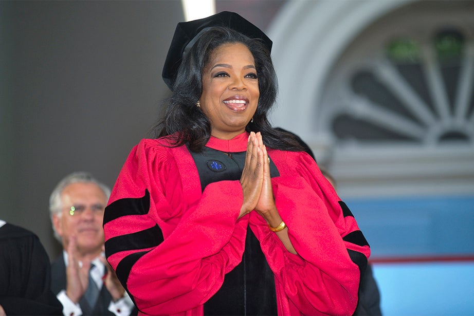 """Oprah Winfrey offers a humble gesture of thanks while being awarded her honorary degree in 2013. Winfrey is an American media proprietor, talk show host, actress, producer, and philanthropist best known for her award-winning talk program """"The Oprah Winfrey Show."""" She was awarded the Presidential Medal of Freedom by President Obama. Jon Chase/Harvard Staff Photographer"""